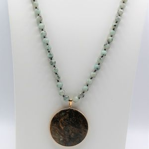 Long knotted green necklace with round pendant
